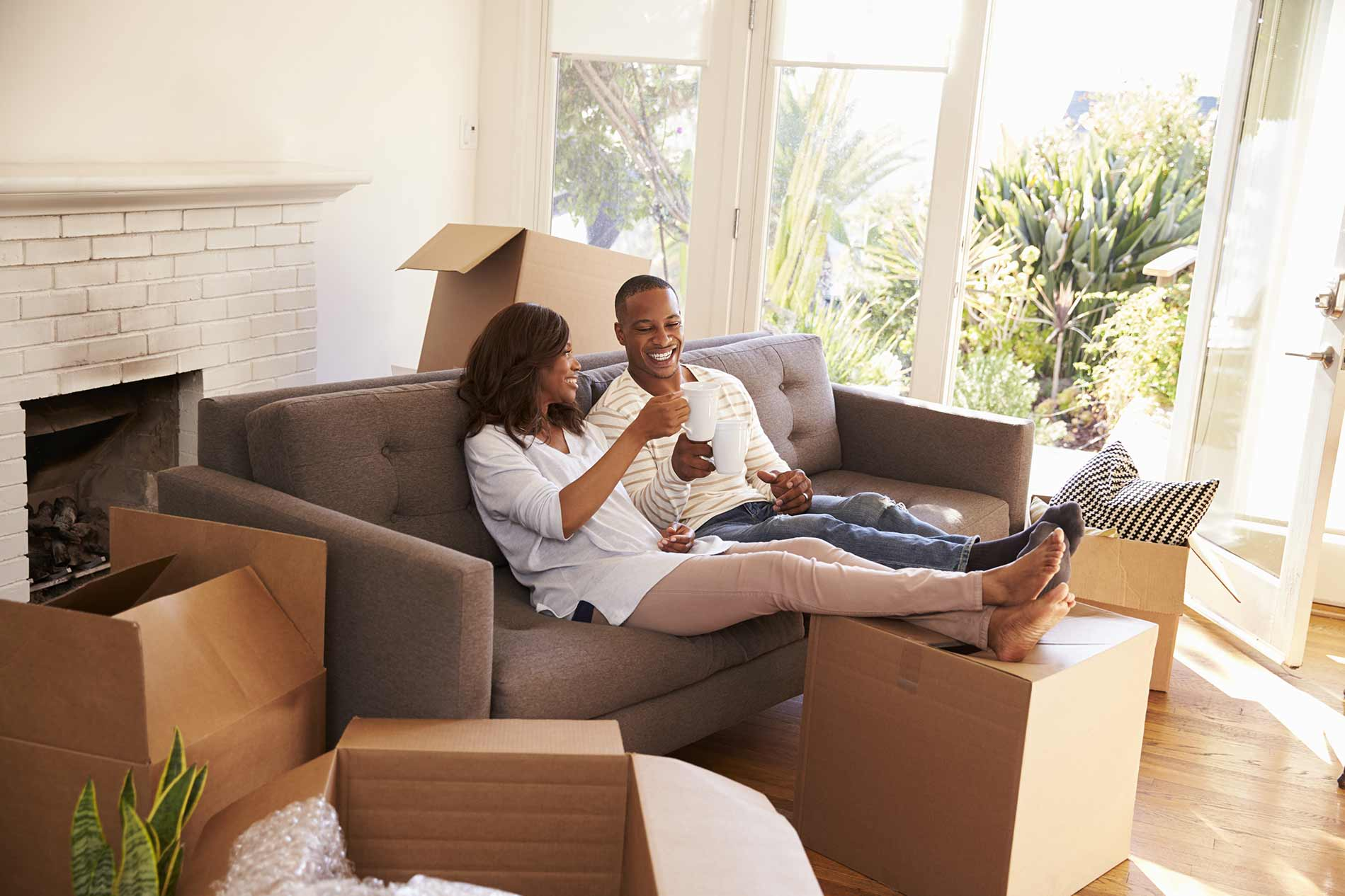 Couple enjoying coffee on couch with moving boaxes